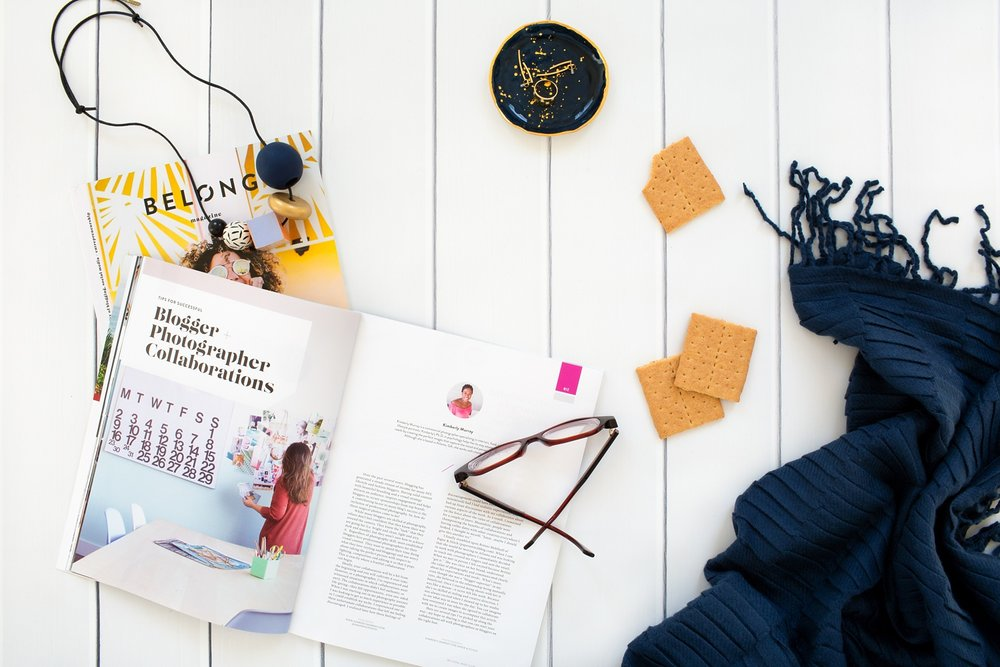 Flat lay image by Kimberly Murray Photography of Belong Magazine, glasses, and a blanket.