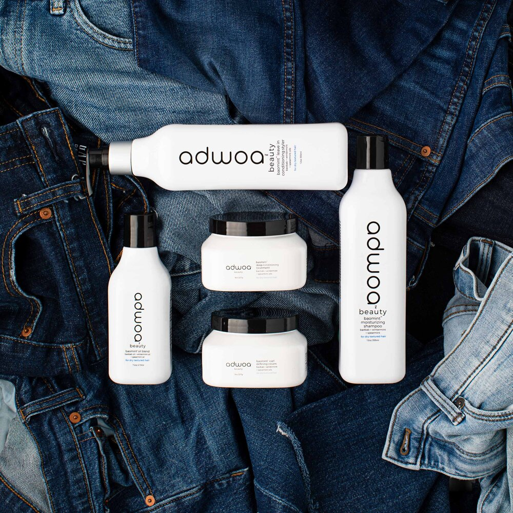 Knolling image of minimalist hair product bottles on jeans.