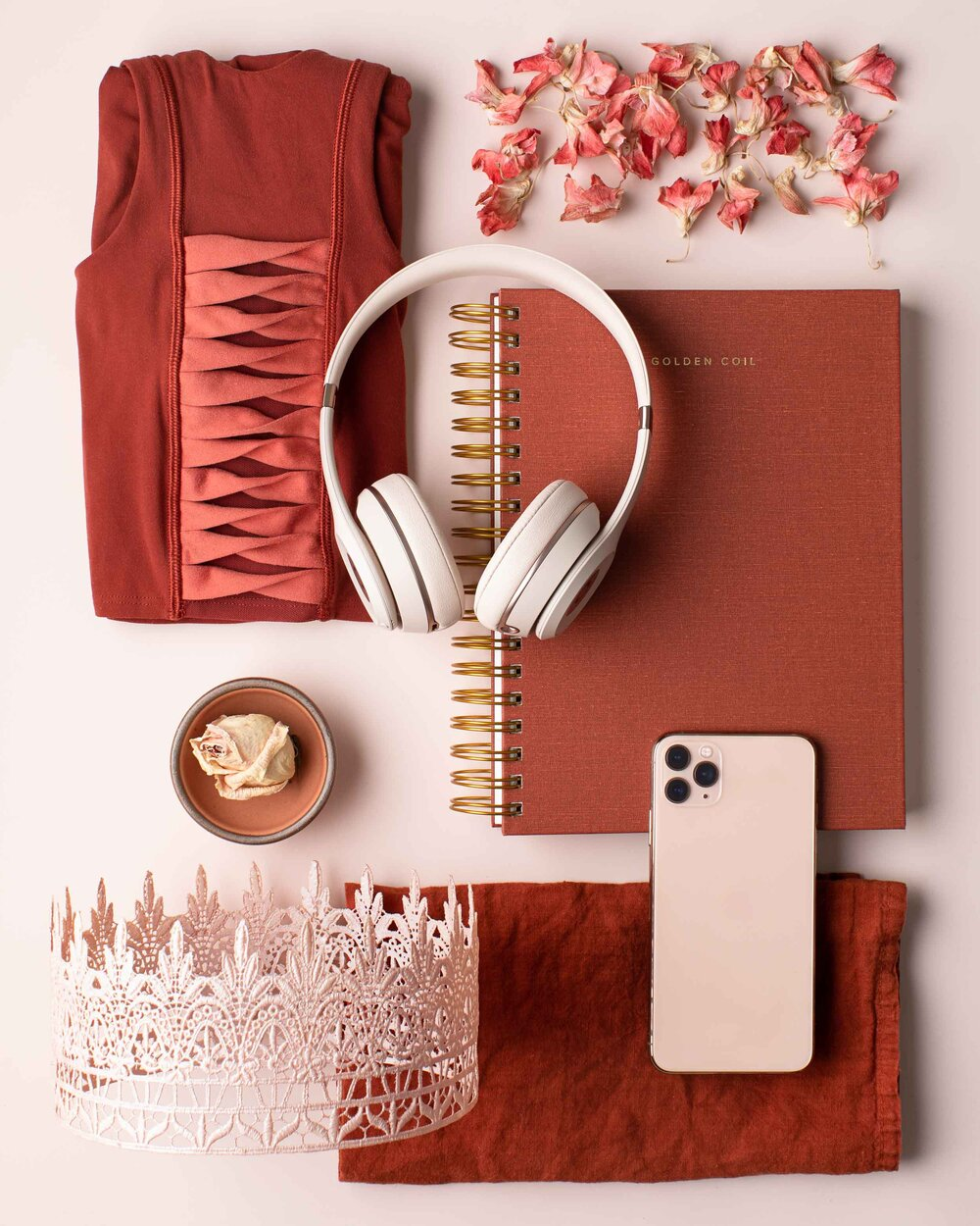Knolling image of rust and blush colored items.